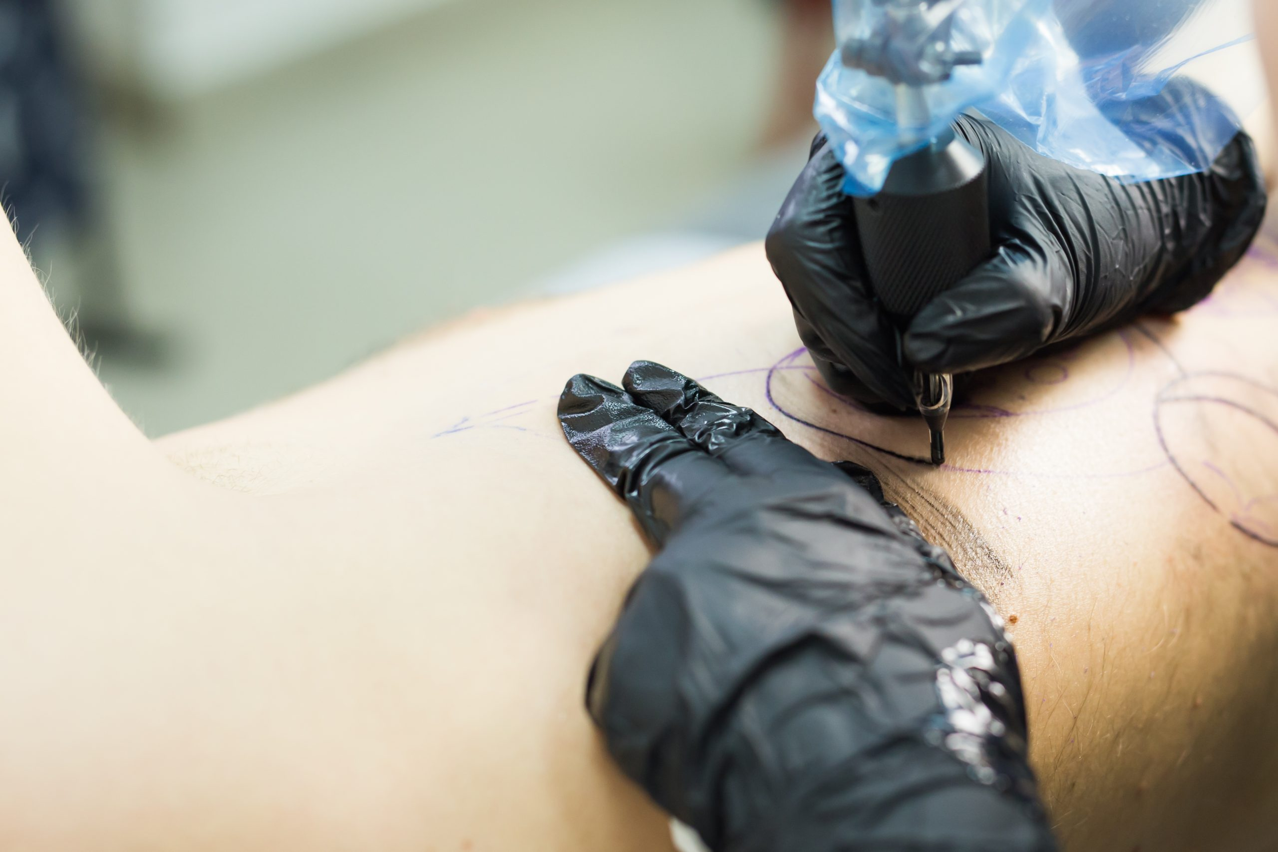 tattooer showing process of making a tattoo, hands holding a tatoo machine